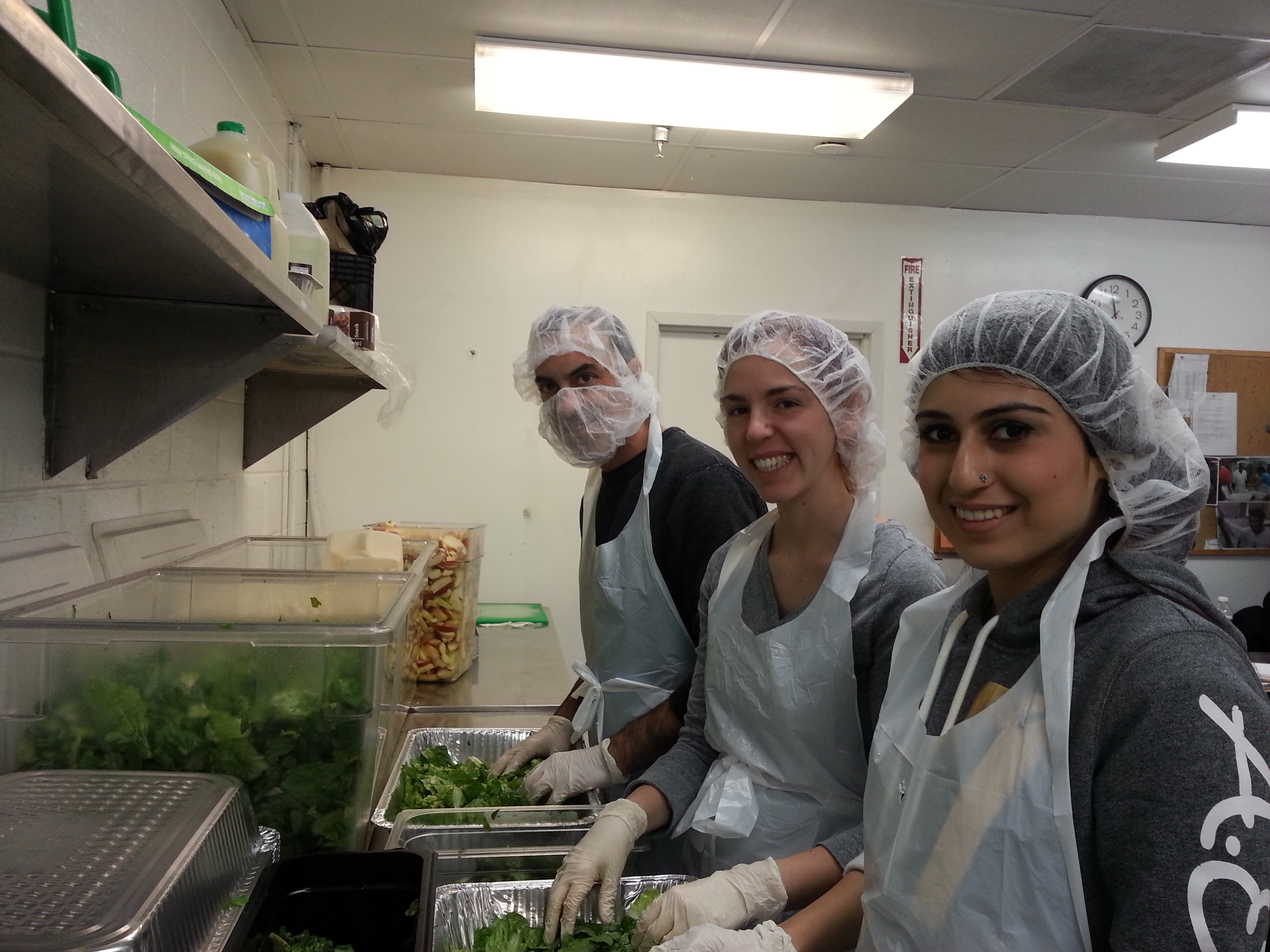 sundas liaqat with other volunteers at dc central kitchen cleaning salad leaves to help prepare meal - Dc Central Kitchen